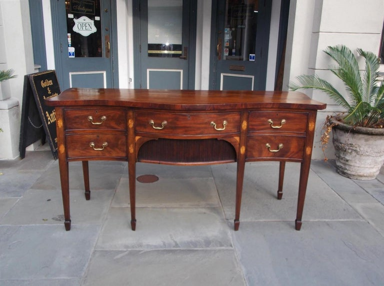 English mahogany serpentine sideboard with a centered drawer over two sliding tambour doors, flanking end drawers, original brasses, oval satinwood patera inlays, and terminating on tapered legs with spade feet, Late 18th century.
