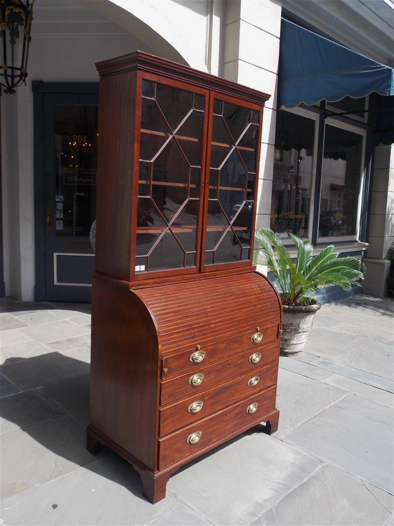 English mahogany secretary with a carved molded dental cornice, two hinged upper case doors revealing three adjustable interior shelves, tambour desk fitted with interior leather tooled writing surface, four lower case graduated drawers with the
