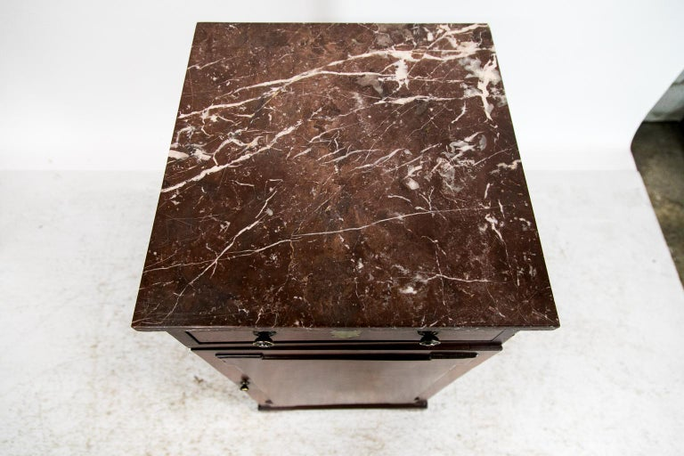 This mahogany marble top silver cabinet has geometric ebony line inlay on the drawer front and ebony edging on the door. The door has a raised molded panel of flame grained mahogany. The interior is fitted with drawers. The interior oval drawer