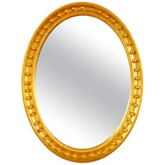 English Mid-19th Century Oval Gold Leaf Mirror with Balls