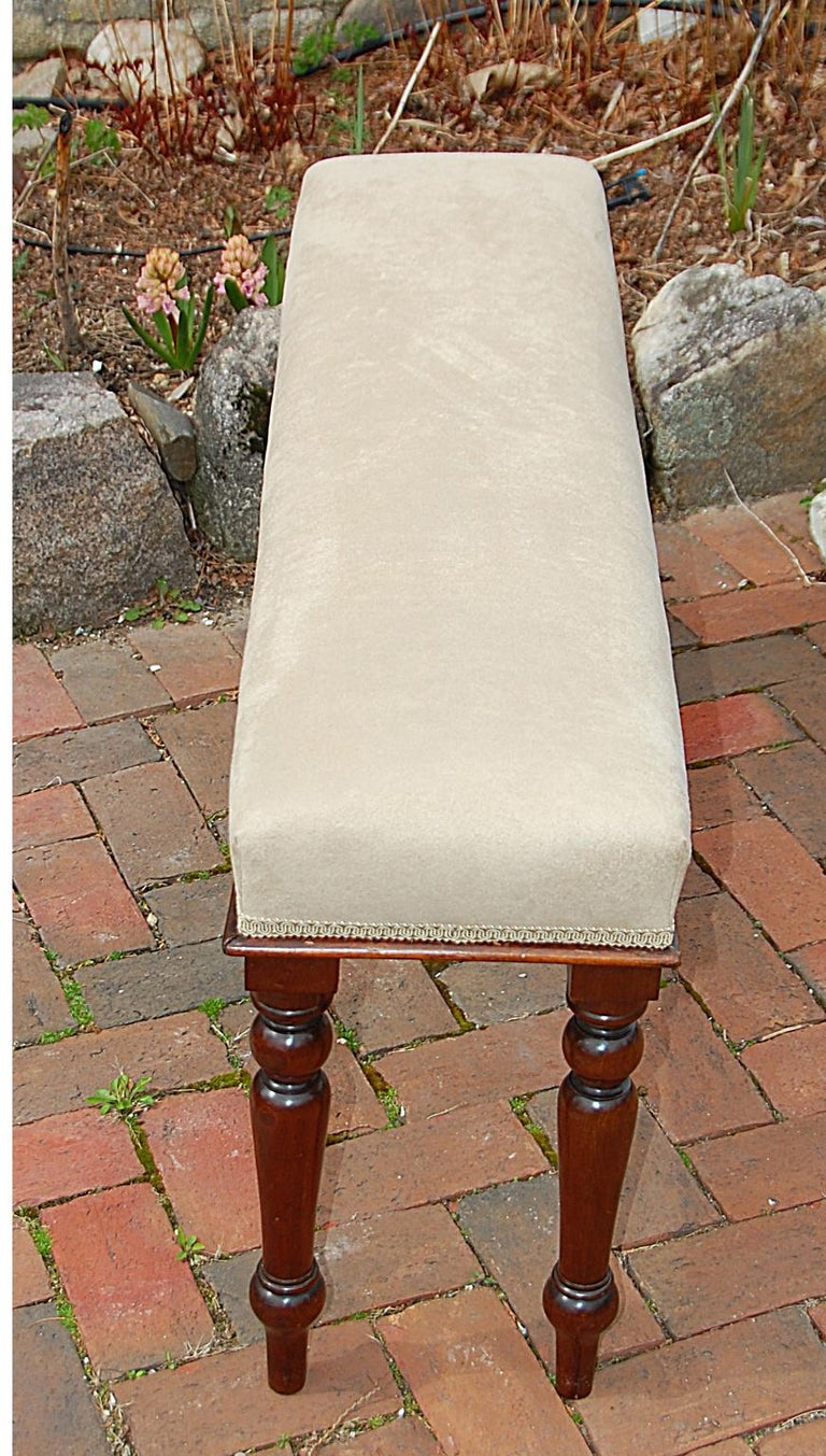 English mid-19th century upholstered bench with turned mahogany legs, and mahogany small molding to seat edge. The newly upholstered bench has a fawn colored ultrasuede fabric. At only 44 inches long this versatile bench can find a home in most