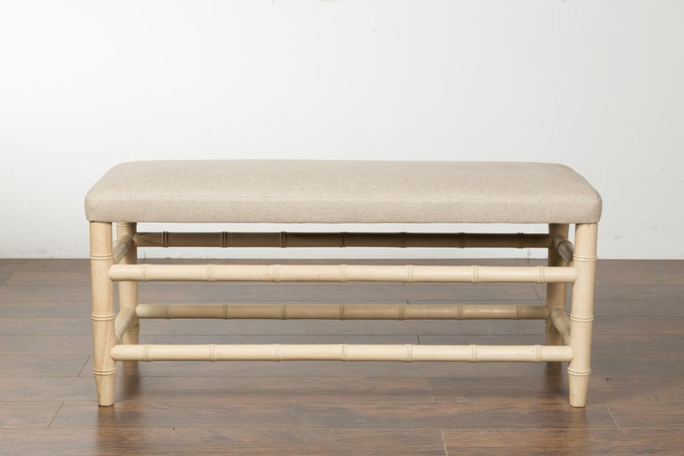 An English vintage bleached walnut faux bamboo bench from the mid-20th century, with new upholstery. Created in England during the midcentury period, this bleached walnut bench features a rectangular seat newly recovered with a neutral toned linen
