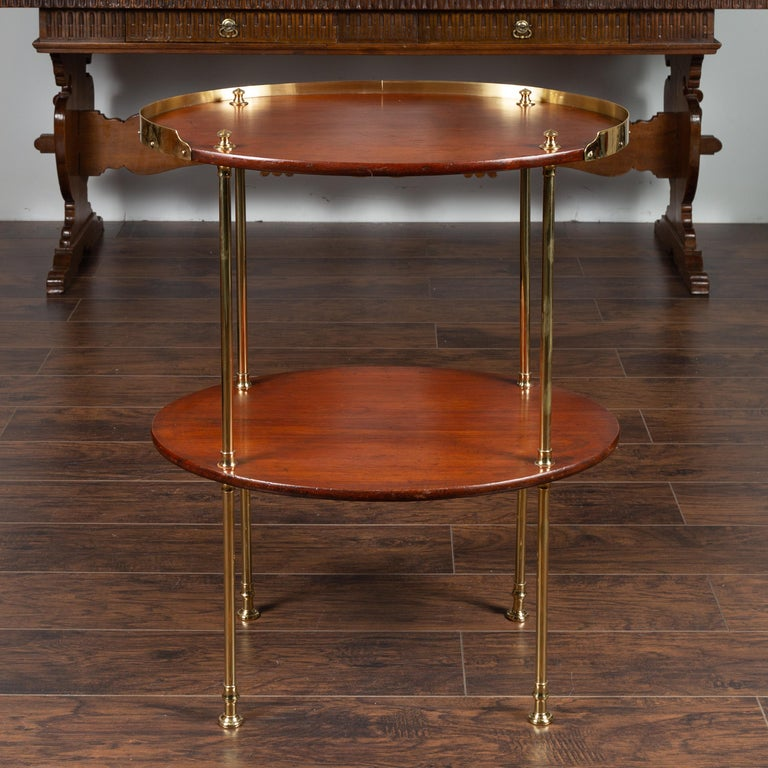 An English mahogany tiered oval table from the mid-20th century, with brass accents. Born in England during the midcentury period, this two-tiered table features an oval top surrounded by a three-quarter brass gallery, supported by brass supports