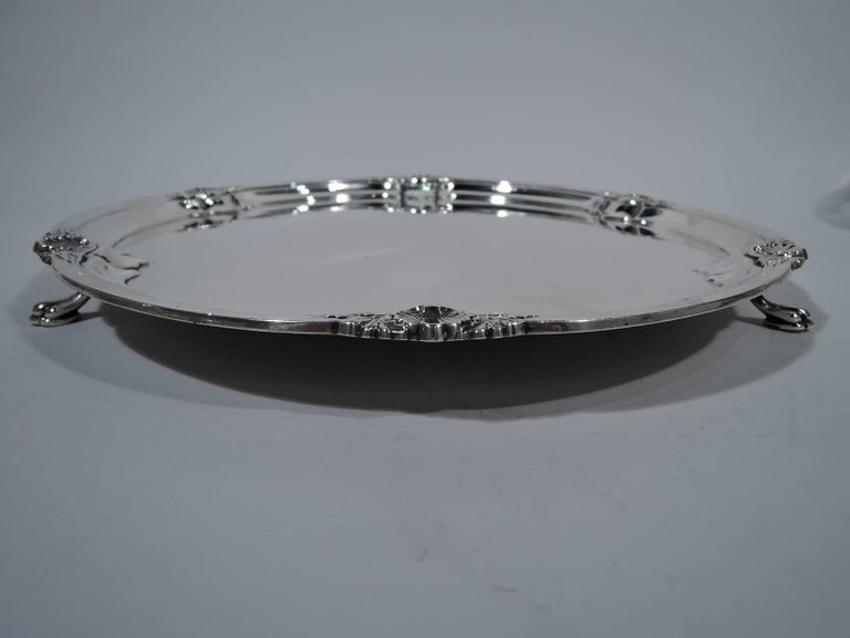 George V sterling silver salver. Made by Cooper Bros & Sons in Sheffield in 1927. Lobed well. Rim molded with applied shells and leaves. Rests on three paw supports. An elegant updating of Georgian motifs. Hallmarked. Weight: 41 troy ounces.