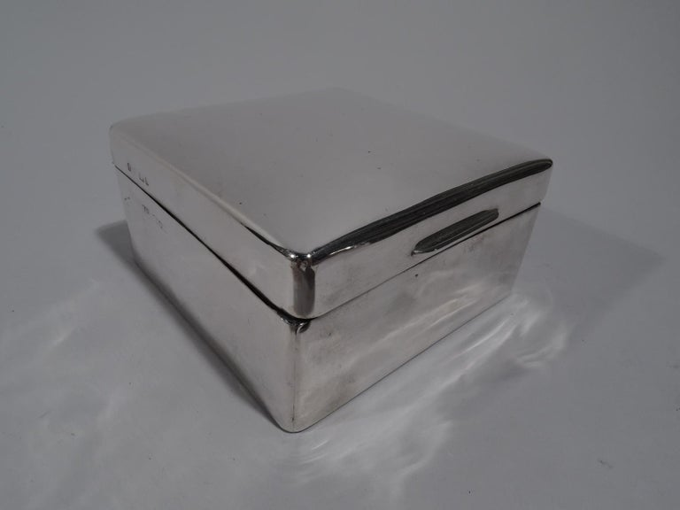 George V sterling silver box. Made by Skinner & Co. in London in 1925. Square with rounded corners. Cover hinged, tabbed, and gently curved. Box and cover interior cedar lined. Box underside leather lined. Fully marked. Gross weight: 6.5 troy ounces.