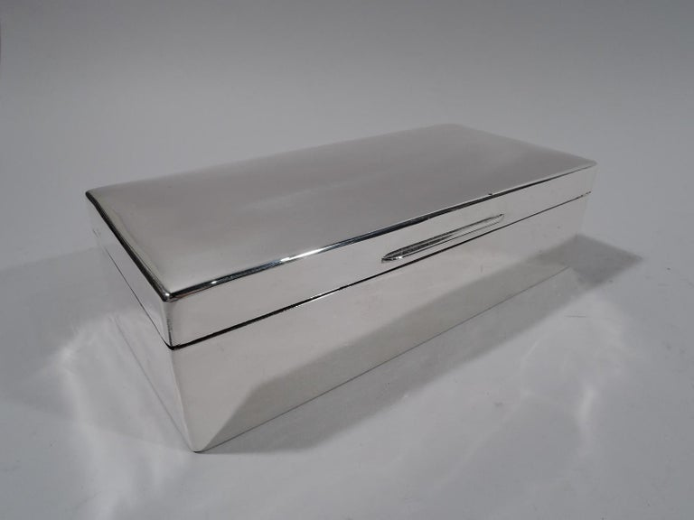 George V sterling silver desk box. Made by Charles Boyton & Son in London in 1924. Rectangular with straight sides. Cover hinged and gently curved with linear tab. Box and cover interior cedar lined and partitioned. Underside leather lined. Fully