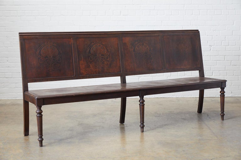 Unique late 19th century English oak bench or settle from the late Victorian period featuring Art Nouveau embossed panels. This unique bench is a transitional piece as it has been decorated with early Art Nouveau designs of stylized flora motifs on