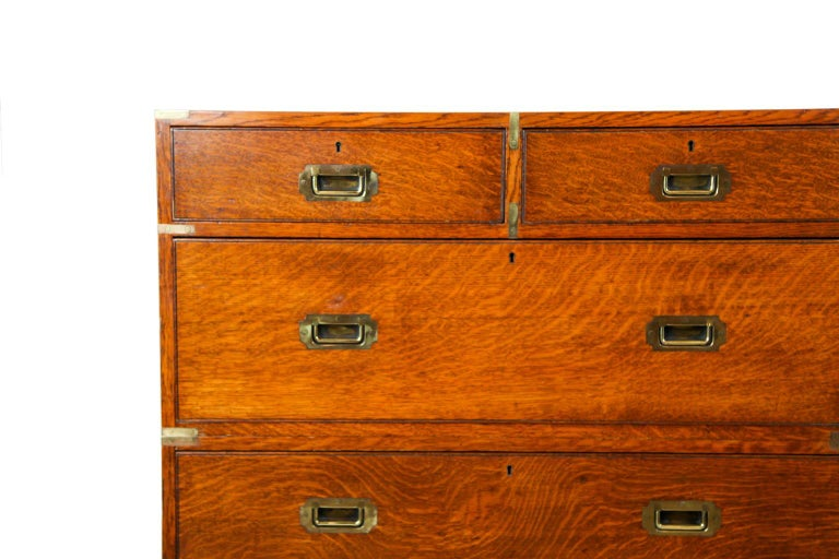 English oak campaign chest, the two section chest with brass top corners and edges, inset Campaign handles, on turned feet.