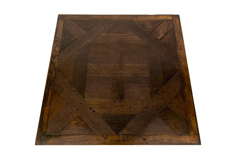 English oak coffee table is made from reclaimed antique flooring and has exposed double peg construction. The top is constructed with geometric patterns resting on four square legs.
