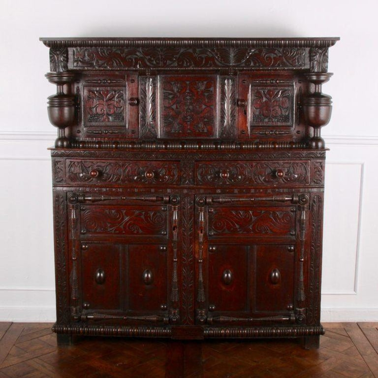 A solid oak sideboard with three tiers, mainly used for displaying plates as a centrepiece. Small storage shelves on top, larger storage areas below, with four drawers. Fashionable in the 16th century. Common in Northern and Southern Europe, circa