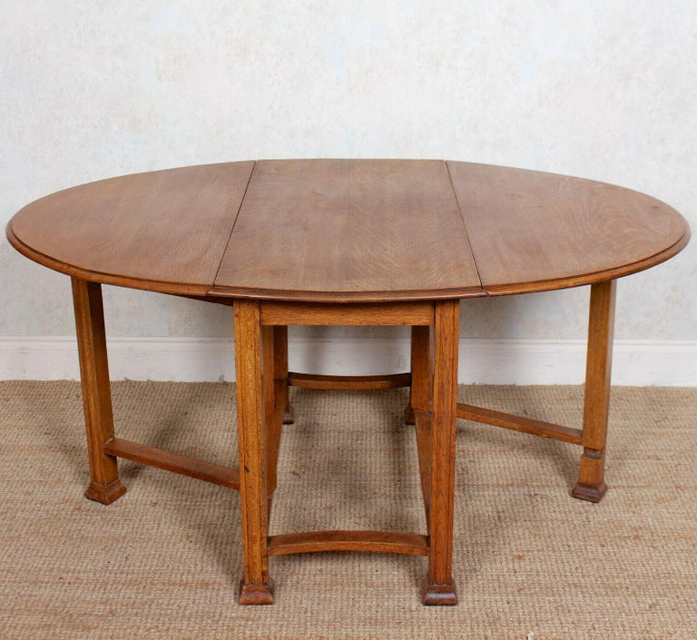 An attractive early 20th century oak gateleg table. The oval planked top with chamfered edges, two drop leaves and raised on well carved chaneled legs and feet united by carved stretchers. England, circa 1920.
