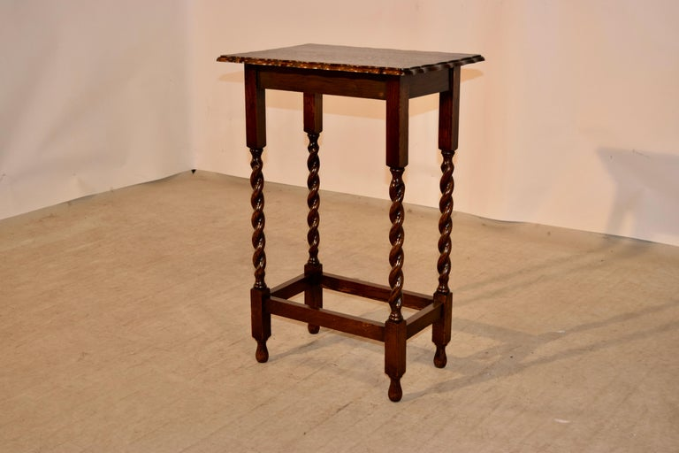 Oak side table from England with a beveled and scalloped edge around the top following down to a simple apron and supported on hand-turned barley twist legs, joined by simple stretchers and raised on turned feet.