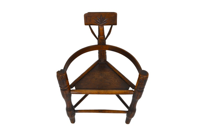 Triangular three-legged primitive chair called Turners' Chair. Made from English oak, this chair has good color and patina. Turners' chairs were made by wood turners in pre-Elizabethan age before joiners took over furniture making from turners and