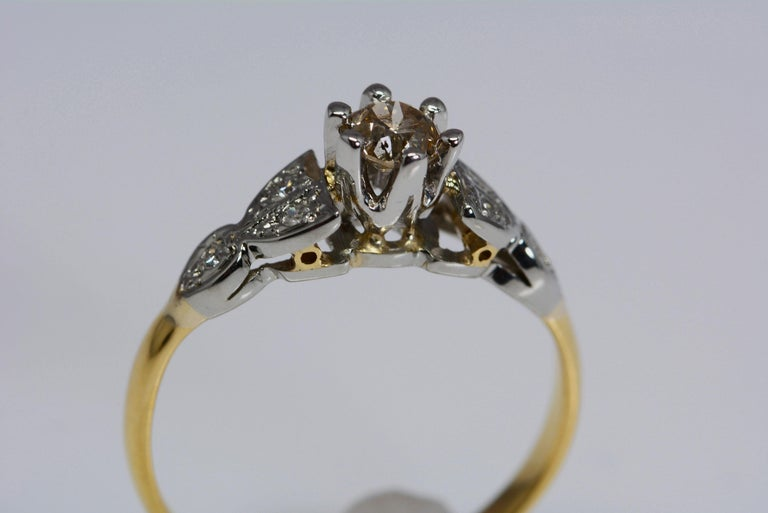 This ring is from the early 20th century and it is of english origin. It is fabricated from 18 karat yellow gold and platinum.  The ring band has 6 single cut diamonds in total, weighing: 0.06 carat total weight;  In the center is 1 old european