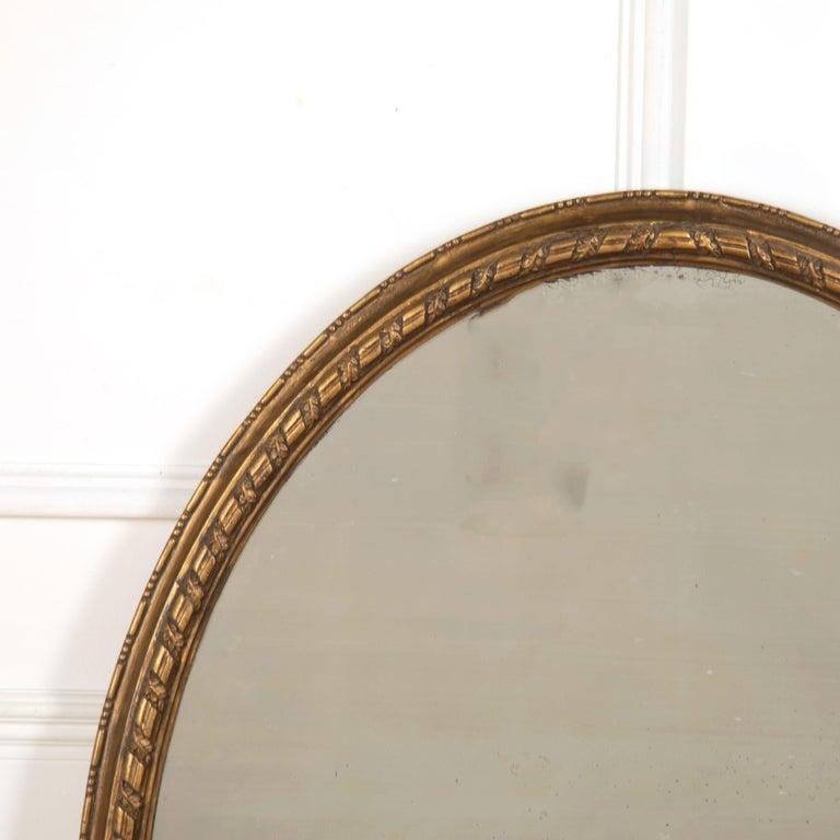 English 19th century oval gilded mirror, circa 1860.