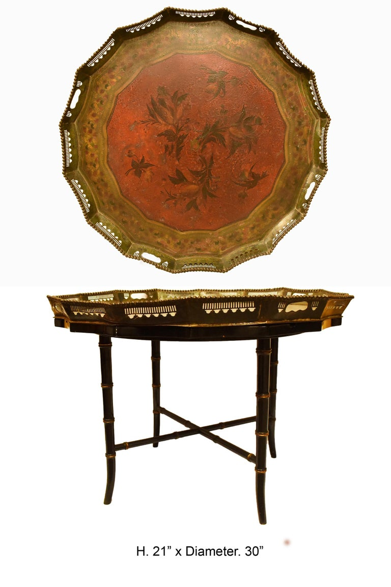 English 19th century painted round tall tray with sixteen sides. The tray is beautifully hand painted tole with floral and leaf motif, resting on later ebonized and parcel gilt bamboo form stand.  The tray is removable.  Measures: Height 21
