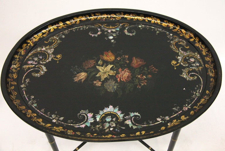 """English papier mâché black lacquer tray on stand, the tray rim decorated with gilt foliate, central floral bouquet surrounded by mother of pearl arabesques and motifs, the later stand with faux bamboo legs connected with """"x"""" stretcher."""