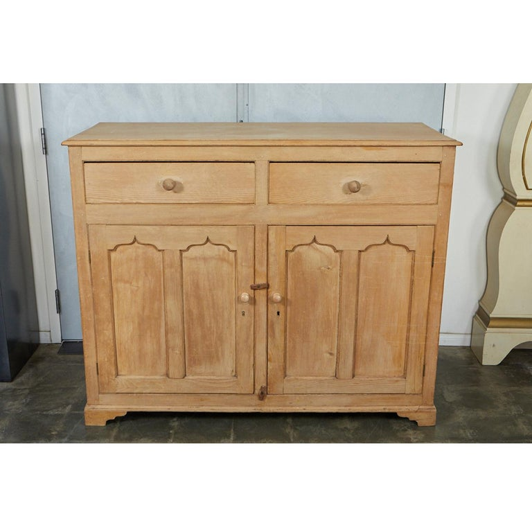 This high cabinet or cupboard has two drawers, two doors and two shelves. The paneled doors and sides are nicely shaped. The piece stands on four shaped feet. The excellent craftsmanship and signs of wear are indicative of a piece from the mid-19th