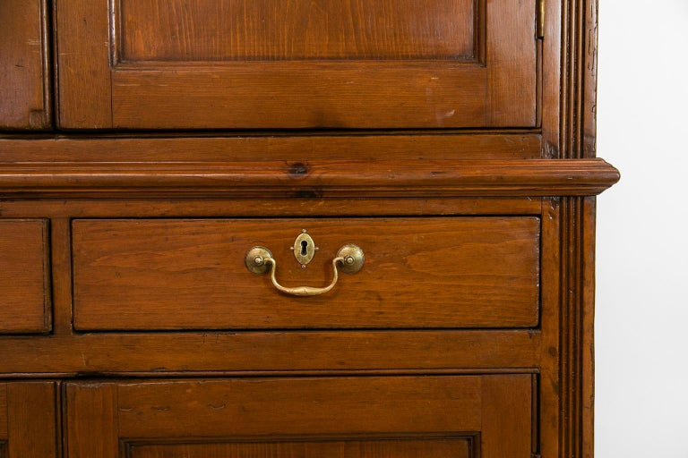 This pine cupboard has exposed peg construction. The top and bottom doors have recessed molded panels. The upper and lower side stiles have carved reeding which terminate in ogee feet.