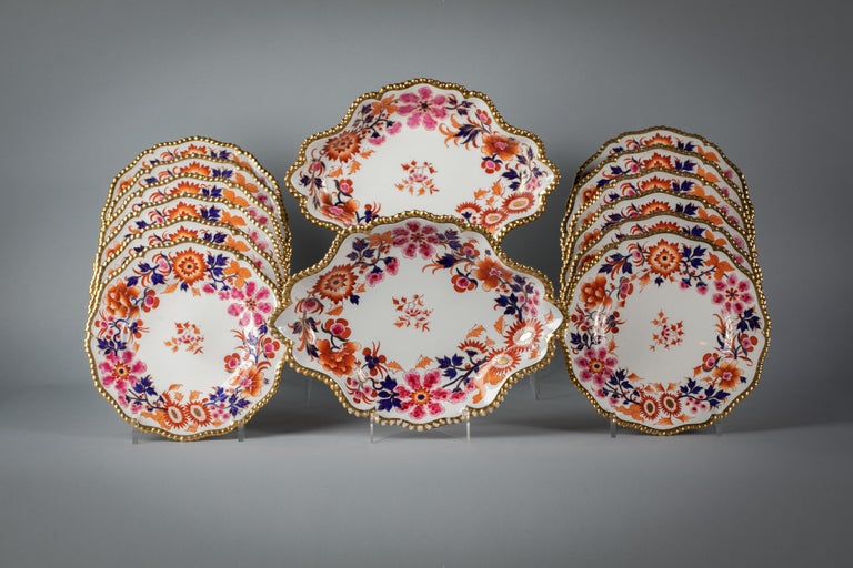 Comprising twelve plates and two lobed oval dishes. Delicately painted in shades of iron red, pink, under glazed blue and gilt. The gadrooned border with heavy gilding. Impressed Flight Barr and Barr.