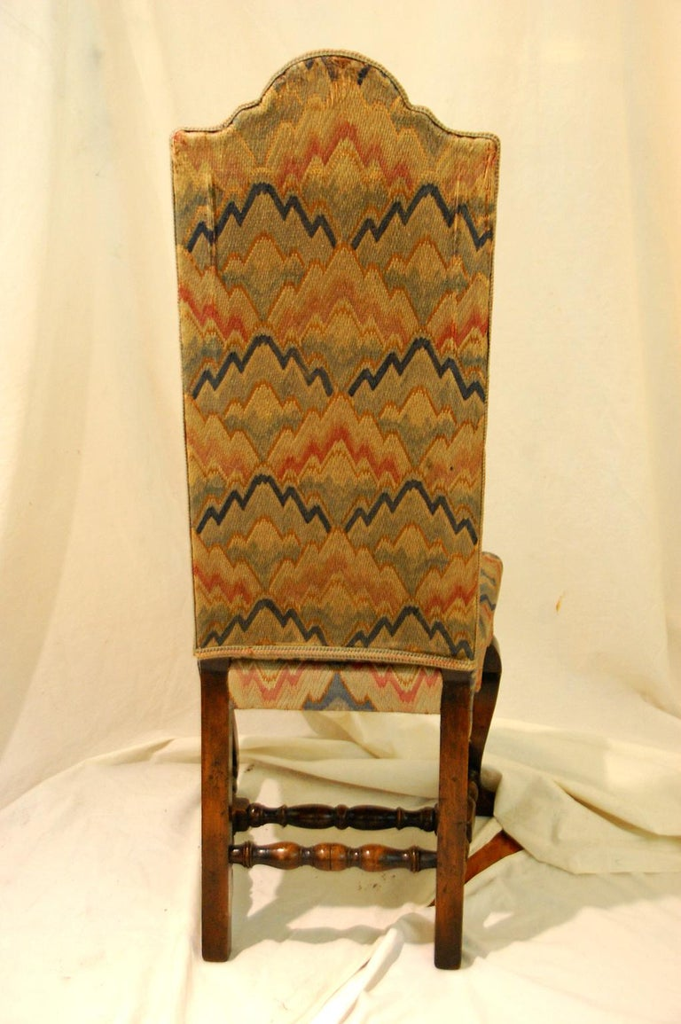 English Queen Anne style set of four walnut high back upholstered side chairs with original flame stitch upholstery (not perfect) in soft blues and corals. These circa 1900 chairs have hand carved cabriole legs and boldly turned H-stretchers,