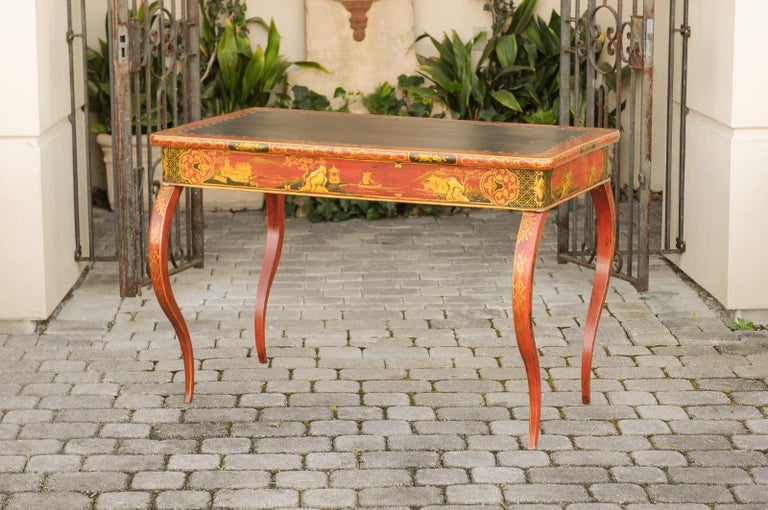 An English Regency period writing table from the early 19th century, with red lacquered, black and gilt chinoiserie decor and cabriole legs. Born in England in the early years of the Regency era, this exquisite table features a rectangular top with