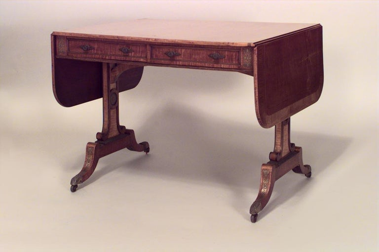 English Regency brass inlaid and mounted satinwood sofa table with tulipwood cross-banded top above two frieze drawers on trestle legs with brass caps and casters, circa 1815.