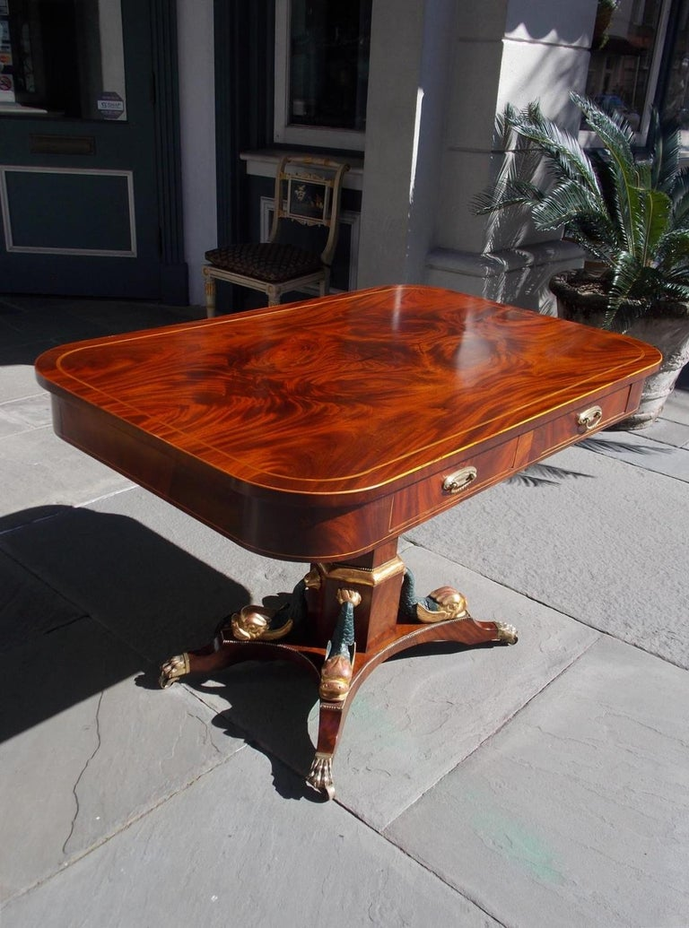 English Regency gilt and satinwood string inlaid four drawer mahogany library table with a book matched flame mahogany top, a hexagon pedestal, flanking gilt and painted dolphins, and resting on the original brass lions paw casters, Early 19th