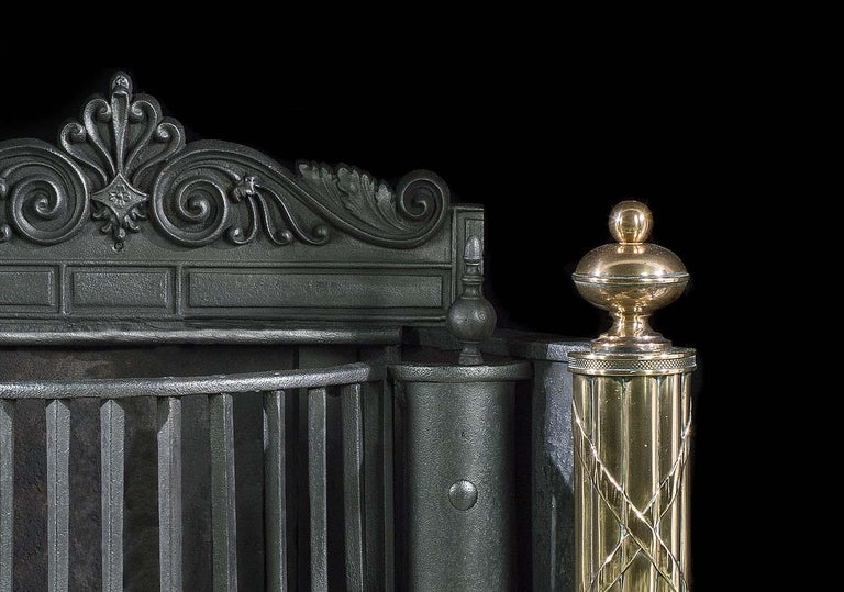A large and impressive English Regency iron, steel and polished brass antique fire basket with a decorative stele crest backplate. The deep bow fronted grate, above a cut and linked medallion skirt, is supported by a pair of large brass standards