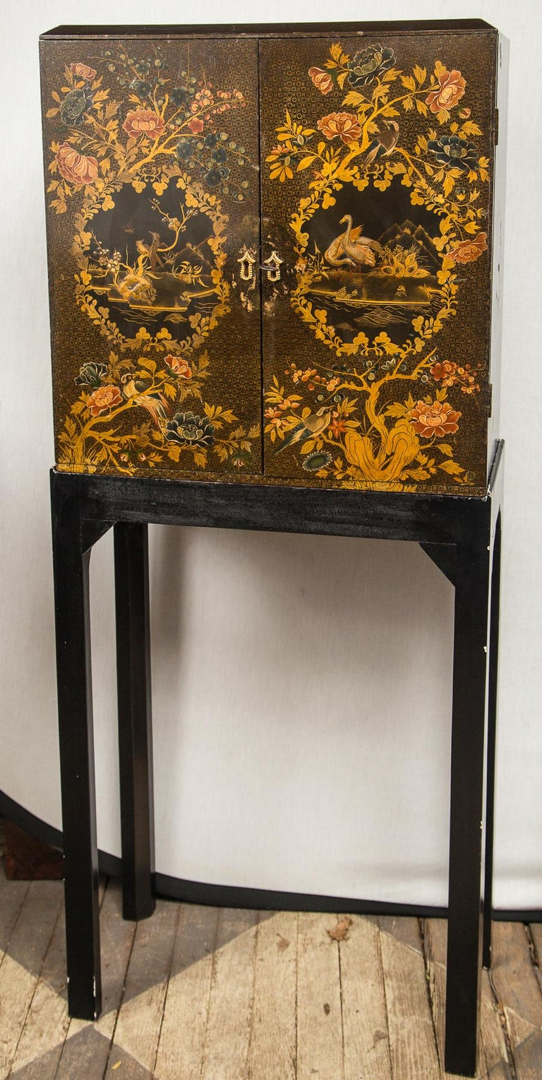 Lacquer in the Japanese style. Double doors, interior with multiple graduated drawers. On a modern Stand. Drawers increase from 1.5 to 2.5 inches in depth. There are 8 drawers behind each door for a total of 16 drawers. Probably made as a collectors