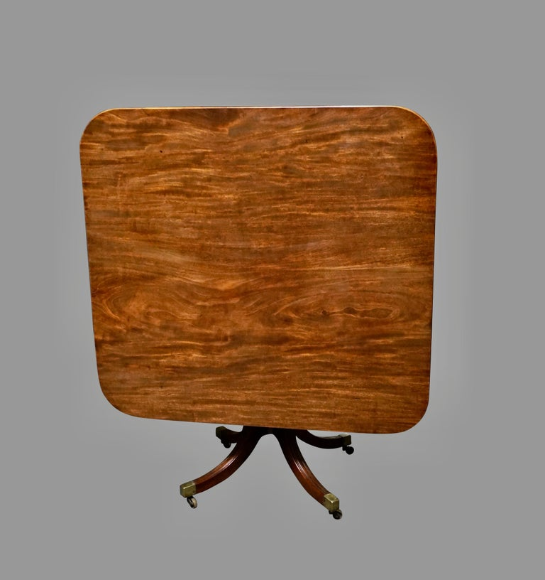 An English figured mahogany breakfast table, the almost square tilt-top with a reeded edge, supported on a reeded downswept quadripartite base ending in brass casters, circa 1815.