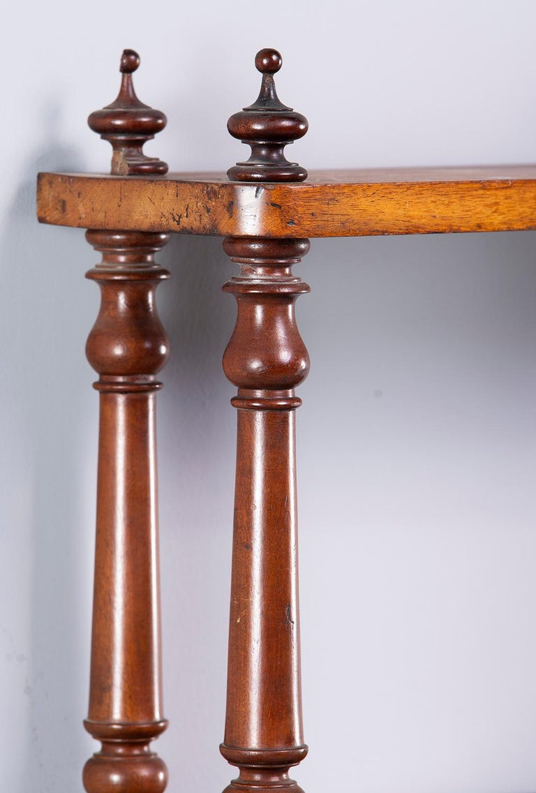 English Regency period mahogany wall shelf is four feet wide with three shelves and fancy turned supports, circa 1830s.