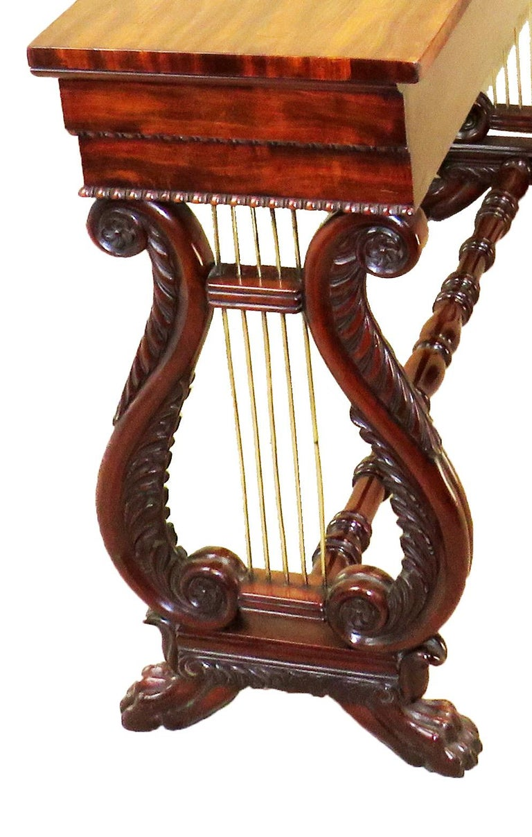A fine quality late regency period mahogany console table of unusually small proportions having well figured top raised on elegant carved and scrolling lyre end supports terminating on carved paw feet united by turned cross stretcher.  (A