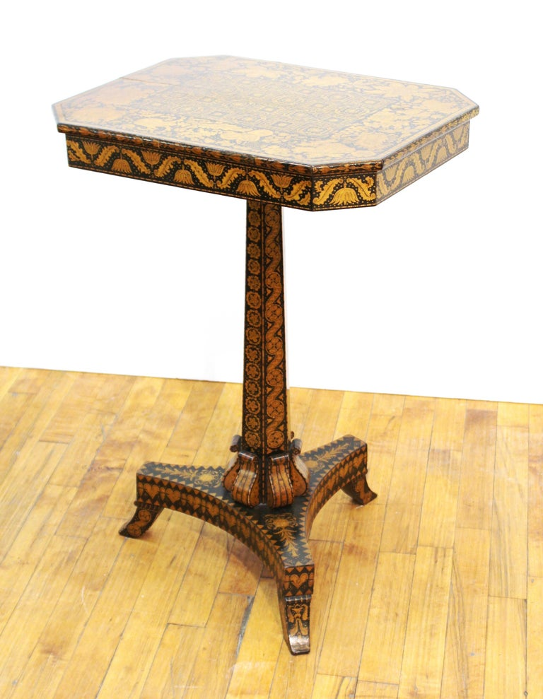 English Regency period penwork wood table with octagonal top raised on tripod base, covered in hand-drawn floral and geometric ornamental decor, circa 1815-1820.