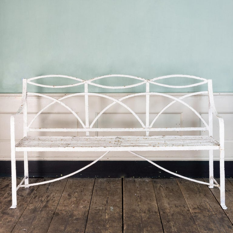 A Regency wrought iron bench or garden seat, of typical reeded and interlaced design, with paw feet to the front.