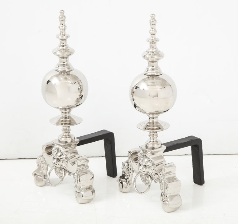 Pair of stylish polished nickel andirons with a lion's head with ring front and tapering spire with blackened iron backs.