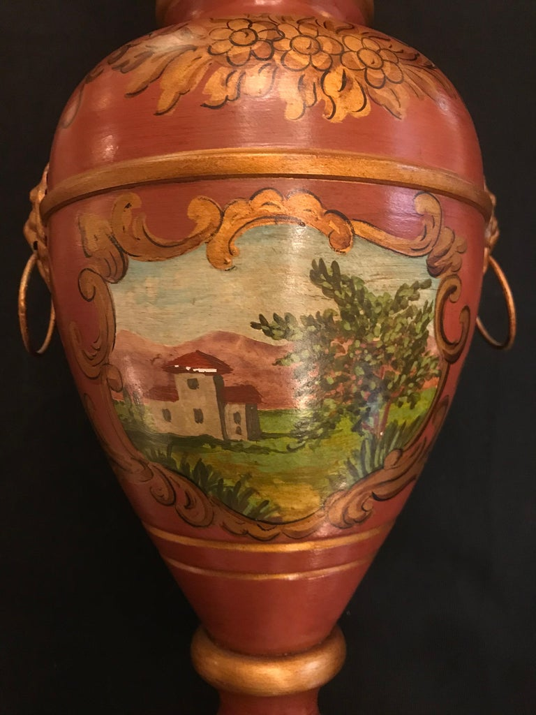 Exquisite English style tole lamp By Gherardo Degli Albizzi featuring a vase shape and square base, with hand-painted neoclassical decoration all-over. Hand-painted leaf decoration adorns all around the base, while on the body of the vase there is a