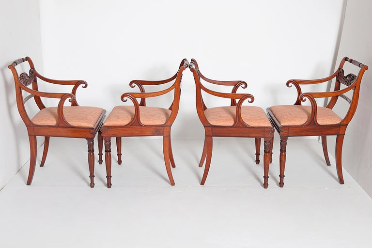 A set of eight (8) English Regency armchairs / dining chairs, Trafalgar design with turned rope twist crest rail and central carved anthemion / palmette back splat with dolphins each side, curvy / shaped armrests, inlaid ebony and boxwood stringing