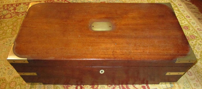 English Regency walnut travelling sloped lap desk box with brass corner mounts and retractable handles. Bone escutcheon lock (no key.) Other features include Fine tooled leather insert and a secret spring loaded compartment inside -see last two