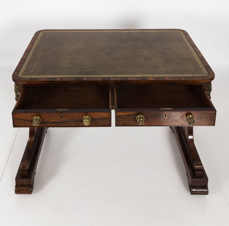 English Regency style two-drawer rosewood writing table from an estate in Hyde Park, NY that features a leather embossed tabletop with some minor staining and scratches, circa 1820. This table also features a trestle base with decorative brass trim
