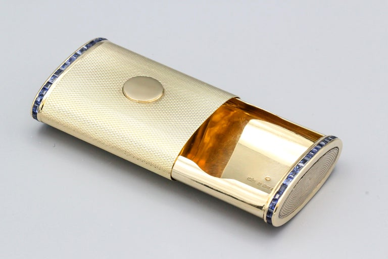 Very fine sapphire and 18k yellow gold rectangular pillbox with sliding mechanism, of English and French origins, circa 1950s. It features calibre cut sapphire along its bordersand an engine turned texture.  Well made and easy to use for larger