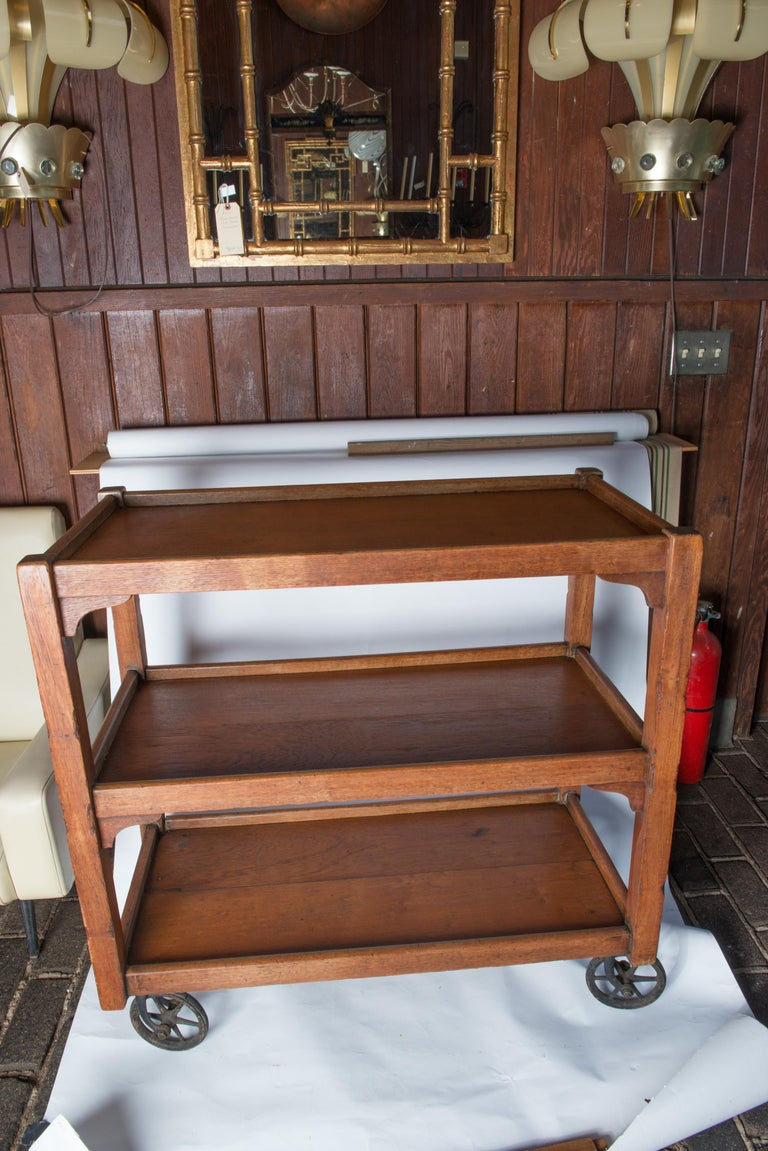 Solid wood English serving cart with original wheels. Both shelves have 14 inch clearance. Wheel diameter is 6 inches.
