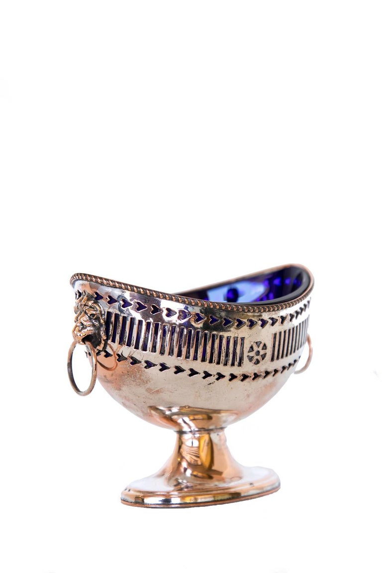English Sheffield Master salt cellar, with the outer shell having a reticulated body with lion head pull handles. The liner is hand blown cobalt blue. The silver has some worn areas.