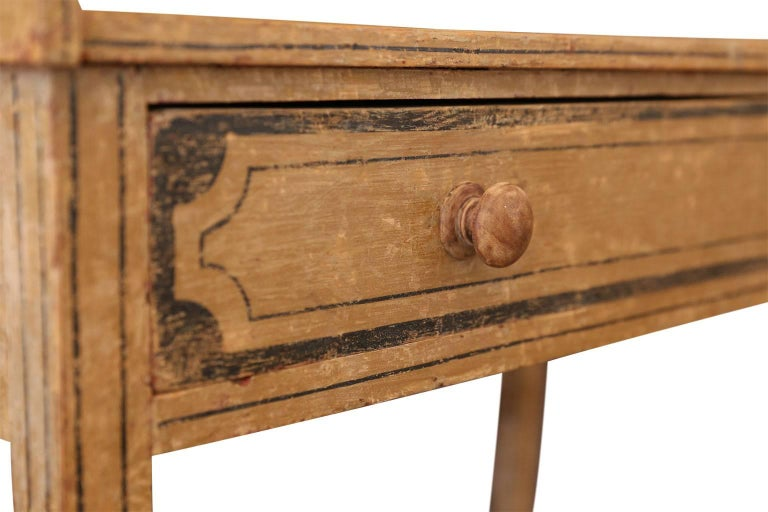 English side table or washstand, with single full length drawer, dry-scraped back to its original 19th century paint and lined decoration. Flat tabletop surface is 28.5 inches in height (three-quarter gallery around tabletop is 33.25 inches in