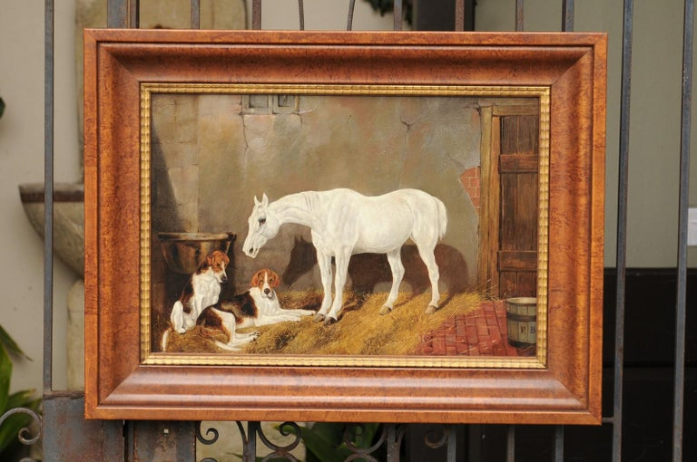 An English barn scene oil painting from the second half of the 19th century, depicting a white horse standing in the front of two hound dogs. This rustic scene strikes immediately by the sobriety of its palette mostly made of brown, red and yellow