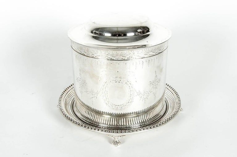 Beautiful English silver plate covered biscuit box/tea caddy with attached footed gallery tray. The Caddy is in excellent condition. The caddy measures 10 inches high with lid open x 8 inches diameter. Maker's mark undersigned.