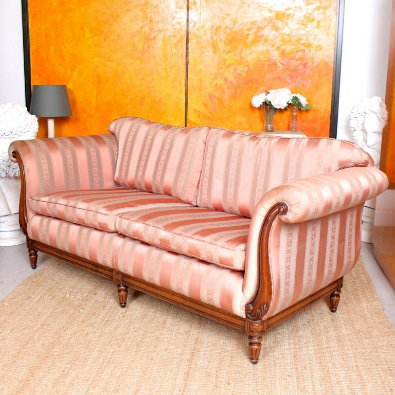 An impressive carved mahogany three-seat sofa offered in good condition. With loose cushions having scroll carved arms with covers and padded apron, supported on a pressed and carved rail raised on six turned tapering fluted legs.