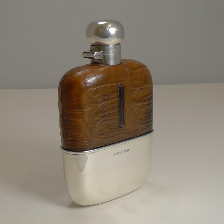 A handsome English sterling silver hip or liquor flask made from sterling silver and the upper half wrapped in Crocodile skin with a lovely cognac color with a good patina.