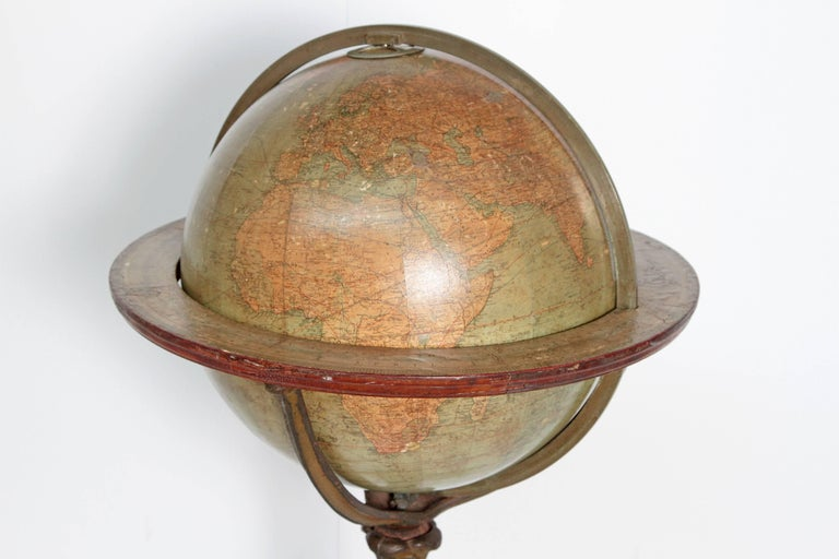 English terrestrial globe on stand by W. & A.K. Johnston, Limited, Geographers; Engravers & Printers, Edinburgh and London. Exquisite cast iron acanthus leaf tripod floor stand base on castors, circa 1890.