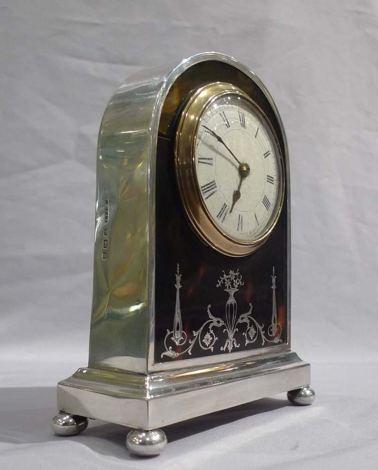 Attractive English silver and tortoiseshell and silver pique mantel clock. The silver case hallmarked for 1921 Birmingham, England. Dome topped silver case on a rectangular base with four silver bun feet. Circular dial within a glass bezel is of